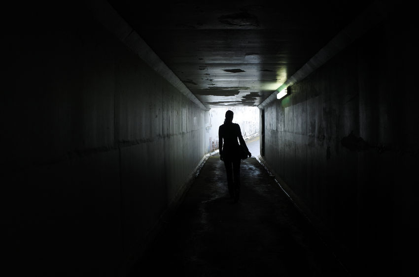 woman walking down a dark corridor